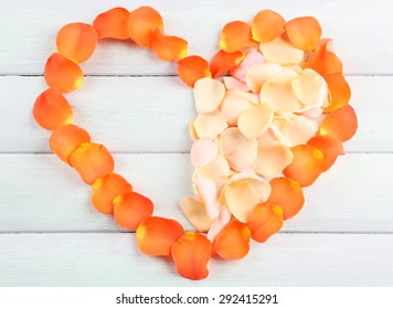 Beautiful heart of rose petals on wooden background