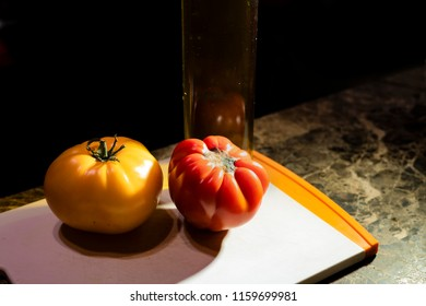 Beautiful heirloom tomatoes with a bottle of olive oil faint in the background.