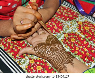 Beautiful henna or mehendi decoration on a hindu bride's hand by a henna artist, against pillow background
