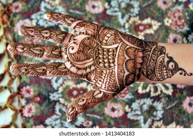Beautiful henna or mehendi decoration on a girl's hand by a henna artist