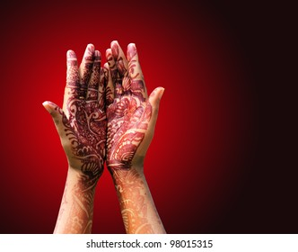 Beautiful henna or mehendi decoration on a hindu bride's hand with hand in praying style.