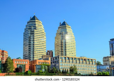 Beautiful high brick skyscrapers, towers and buildings in white and orange with a sun flare. View of the Dnipro city in spring and summer, Dnepropetrovsk, Ukraine