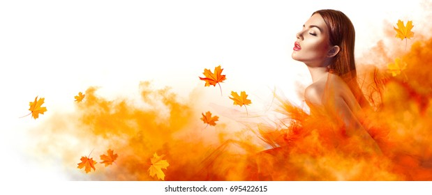 Beautiful High fashion woman in autumn yellow dress with falling leaves posing in studio. Gorgeous brunette model girl with beautiful make-up, Wearing Stunning evening dress with long gown of tulle.