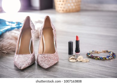 Beautiful high heeled shoes and accessory for party on floor