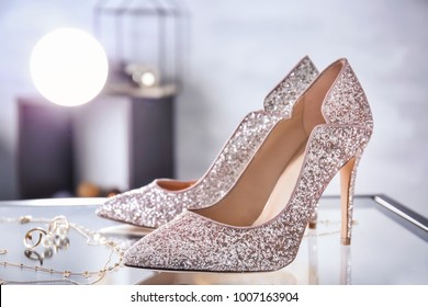 Beautiful high heeled shoes and jewelry on table