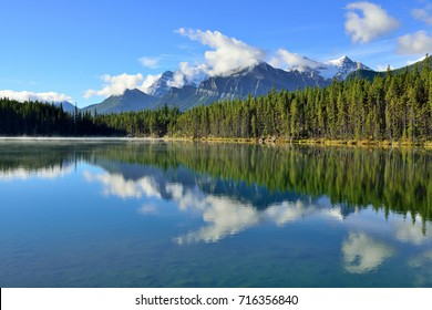 Beautiful high mountains of the Canadian Rockies reflecting in an alpine lake along the Icefields Parkway between Banff and Jasper