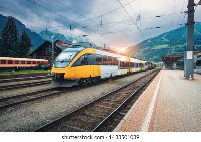 Beautiful high speed train on the railway station in mountains at sunset in summer. Orange modern commuter train on the railway platform. Industrial landscape with railroad. Passenger transportation