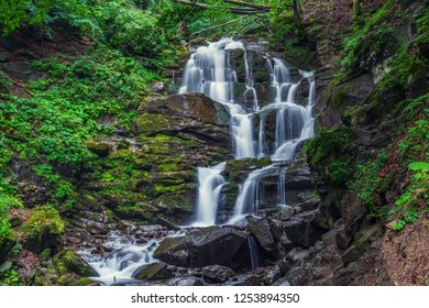 Beautiful high waterfall deep in the Carpathian mountains. Streams of water, wet stones with green grass and moth