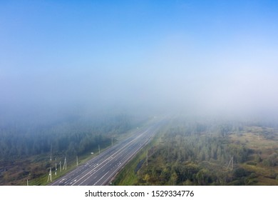 Beautiful hight way road high angle beautiful view of the fog over the road on an early summer morning in central Russia. Bird's eye view of the road and skyline.