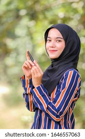 Beautiful hijab girl wearing modern dress holding eyeliner over green background. Beauty product shoot concept.