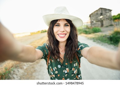 Beautiful hiker young woman, wearing flowered shirt, taking a selfie photograph outdoors