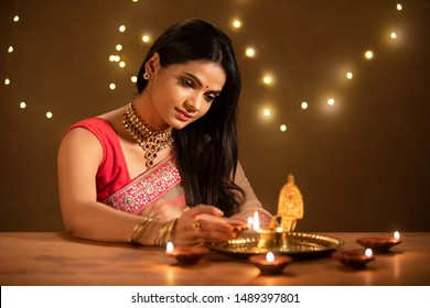 Beautiful Hindu Indian young women lightening deepa on Diwali day.