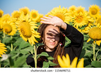 beautiful hippie girl with dreadlocks squinting against the sunlight in a field with sunflowers. happy girl on nature in summer.