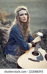 Beautiful hippie girl with guitar sitting on grass near stone