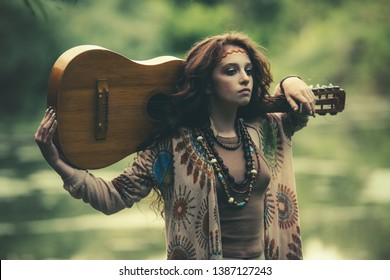 Beautiful hippie girl holding a guitar on his shoulders in the countryside. Contemporary bohemian style. Spirit of freedom. Fashion shot. Bohemian, bo-ho style.