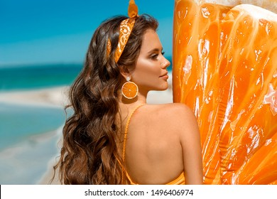 Beautiful hippie girl portrait with orange earring by Inflatable pool float mattress on tropical beach. Brunette with long healthy curly hair and makeup on summer vacation.