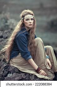 Beautiful hippie girl sitting on stone. Boho fashion style