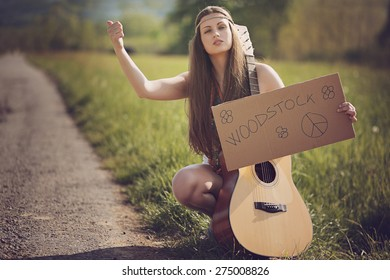 Beautiful hippie with guitar hitchhiking for Woodstock . Warm summer tones
