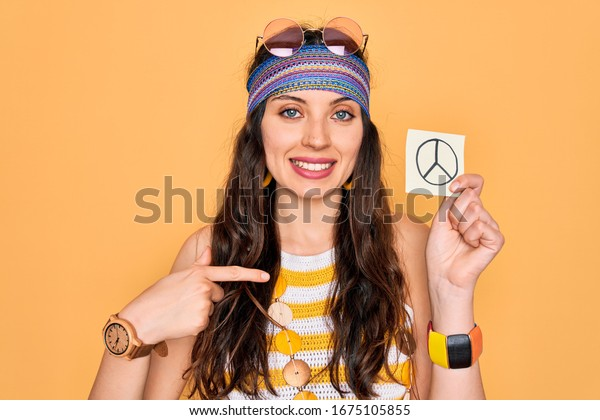 Beautiful hippie woman with blue eyes wearing sunnglasses holding peace symbol reminder with surprise face pointing finger to himself