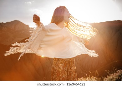 Beautiful hippie young beautiful woman with red hair dressed in boho style. Beautiful movie series at sunset. The idea of freedom