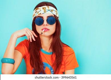 Beautiful hippy girl portrait smoking and wearing sunglasses
