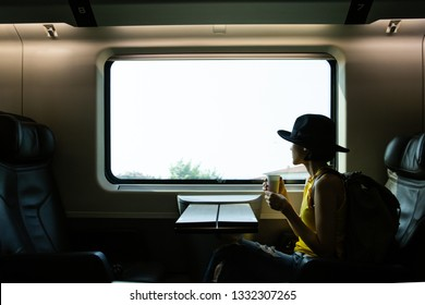 A beautiful hipster asian woman traveling on the train. Sitting on the black leather cozy comfort seat in the business class of the train in Europe and holding camera, wearing black hat.Tourist t