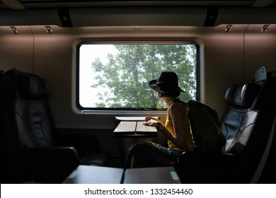 A beautiful hipster asian woman traveling on the train. Sitting on the black leather cozy comfort seat in the business class of the train in Europe. Tourist travel concept.