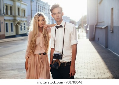 Beautiful hipster couple closeup summer evening portrait on the street. A man photographer with vintage film camera