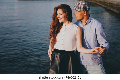 A beautiful hipster couple is standing by the sea.