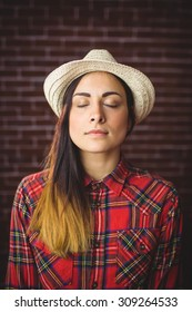 Beautiful hipster with eyes closed on red brick background