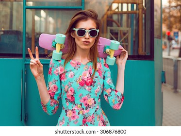 Beautiful hipster fashion young woman model posing with a pink skateboard on city background in vogue sunglasses