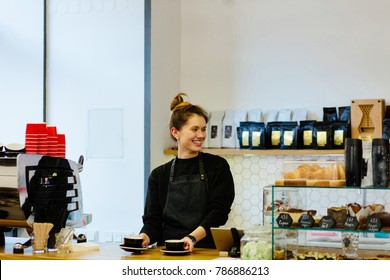 Beautiful hipster female barista with a two cups on coutner, looking away and smiling to someone while standing near the bar counter in modern cafe interior.