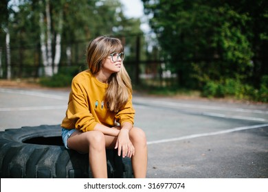 Beautiful hipster girl sitting on the wheel of the truck