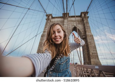 Beautiful hipster girl taking selfie on Brooklyn Bridge, New York. Pretty female student takes funny picture for her travel blog.