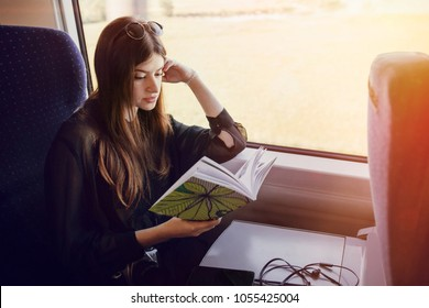 beautiful hipster girl traveling by train and holding book. stylish happy woman reading book at window light in train. travel and transportation. space for text