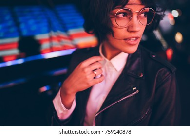 Beautiful hipster girl in trendy apparel looking away enjoying free time outdoors in evening city, attractive brunette female resting at night downtown with neon lights standing near publicity area