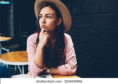 Beautiful hipster girl in trendy hat spending time in cafe interior pondering on plans for work, stylishly dressed young woman concentrated on idea for article sitting at table with pen looking away