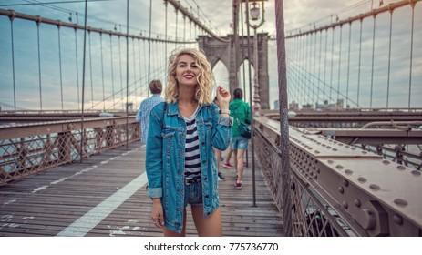 Beautiful hipster girl walking on Brooklyn bridge in New York City
