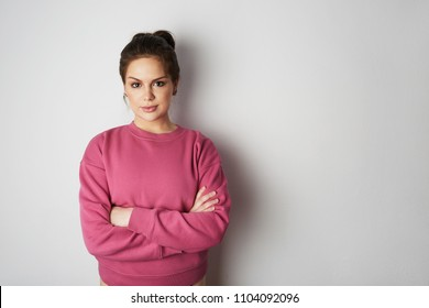 Beautiful hipster girl wearing pink hoody with space for your logo or design. Mock-up of pink hoody on white empty wall in the background. Copy paste text space