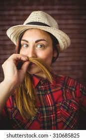 Beautiful hipster holding hair as mustache on red brick background