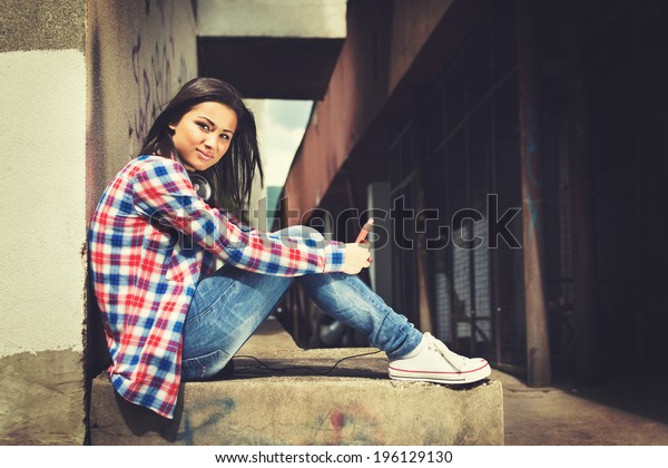 Beautiful hipster mixed race teenage girl sitting in urban environment with smart phone and headphones looking at camera. Contemporary lifestyle concept.