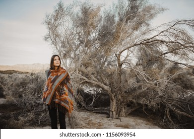 Beautiful hipster traveler girl in gypsy look in desert nature.  Artistic photo of young hipster traveler girl in gypsy look, in Coachella Valley in a desert valley in Southern California.