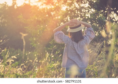 beautiful hipster woman standing near green tree plant and sunset with vintage toned. Women lifestyle enjoy with nature.