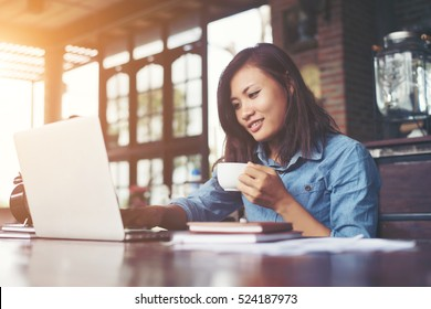 Beautiful hipster woman using laptop at cafe while drinking coffee, Relaxing holiday concept.