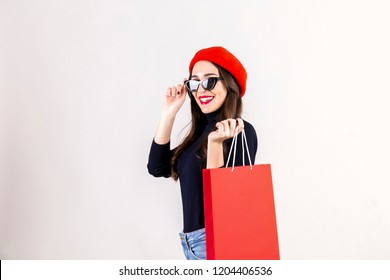 Beautiful hipster young woman with bright red lipstick makeup, wearing black turtleneck, mom jeans & red beret, holding blank shopping bag. Autumn holiday sale season concept. Background, copy space