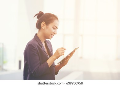 Beautiful hipster young woman wear white lace dress using Ipad or smart phone whith sitting has office blur background to explore website. technology concept