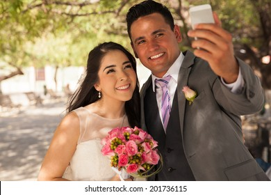Beautiful Hispanic bride and groom taking a selfie with a mobile phone outdoors