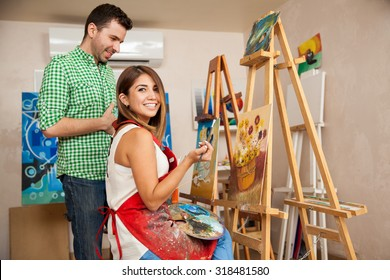 Beautiful Hispanic brunette working on a painting and getting some advice from her teacher at an art school