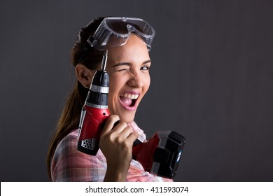 Beautiful Hispanic carpenter woman holding a power drill, Gray Background