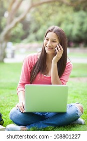 A beautiful hispanic college student talking on the phone working on her laptop on campus